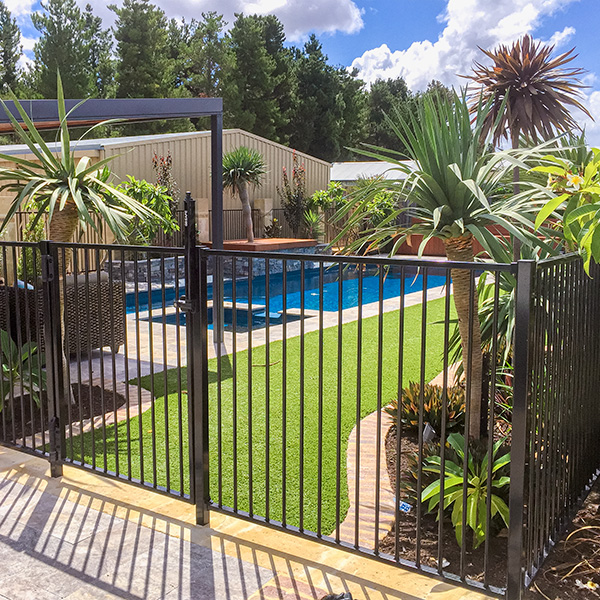 Railing pool fence with entry gate.